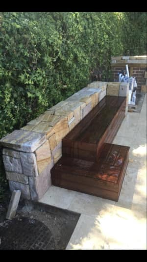Stunning Australian Landscapes Pic 3 - Custom mixed stone feature back rest With a timber bench seat surrounding this pool in Cheerybrook NSW